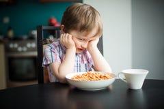O rapaz pequeno ofendido recusa comer o comensal Fotografia de Stock