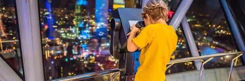 O rapaz pequeno olha a arquitetura da cidade de Kuala Lumpur Vista panorâmica da noite da skyline da cidade de Kuala Lumpur em ar foto de stock royalty free