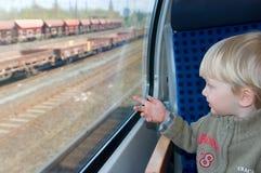 O rapaz pequeno olha no indicador do `s do trem Imagens de Stock