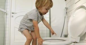 O rapaz pequeno olha no toalete video estoque
