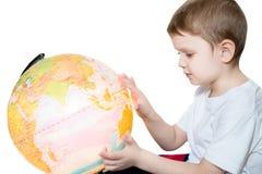 O rapaz pequeno olha o globo imagens de stock royalty free