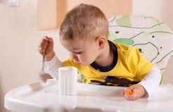 O rapaz pequeno olha um frasco do yogurtini que guarda uma colher Imagens de Stock Royalty Free