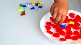 O rapaz pequeno perfura doces na forma do cora??o com os bot?es dos artigos de papelaria de cores brilhantes video estoque