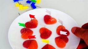 O rapaz pequeno perfura doces na forma do cora??o com os bot?es dos artigos de papelaria de cores brilhantes filme