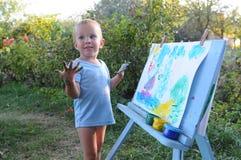 O rapaz pequeno pinta uma imagem imagem de stock royalty free