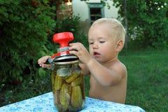 O rapaz pequeno preserva pepinos Imagem de Stock Royalty Free