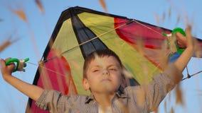 O rapaz pequeno que está entre a grama guarda um papagaio do brinquedo sobre sua cabeça e a espera do vento filme