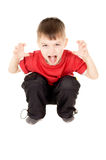 O rapaz pequeno que grita e writhe uma cara imagens de stock