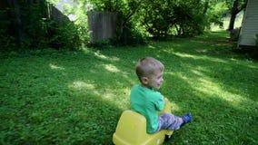 O rapaz pequeno que joga no campo de jogos desliza para baixo de um monte 4k vídeos de arquivo