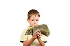 O rapaz pequeno que olha uma pilha de 100 dólares americanos fatura e pensa Imagem de Stock Royalty Free