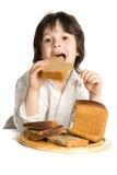 O rapaz pequeno que que come um pão na mesa imagens de stock royalty free