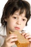 O rapaz pequeno que que come um pão na mesa fotos de stock royalty free