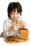 O rapaz pequeno que que come um pão na mesa fotografia de stock royalty free