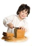 O rapaz pequeno que que corta um pão na mesa imagens de stock