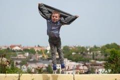 O rapaz pequeno que salta acima do revestimento de revelação gosta das asas fotografia de stock