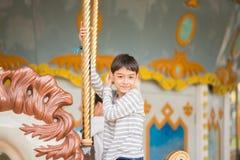O rapaz pequeno que senta-se dentro casa-se vai circularmente no parque de diversões imagem de stock