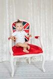 O rapaz pequeno que senta-se em uma cadeira gosta de um real imagem de stock