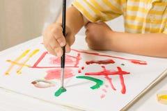 O rapaz pequeno que senta-se em uma tabela pinta uma imagem de uma folha branca Foto de Stock