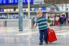 O rapaz pequeno que vai em férias tropeça com a mala de viagem no aeroporto Imagem de Stock