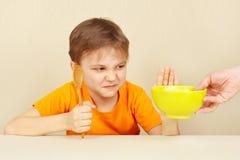 O rapaz pequeno recusa comer o cereal Fotografia de Stock
