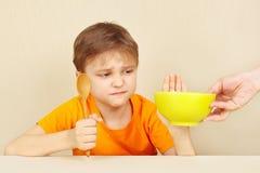O rapaz pequeno recusa comer o papa de aveia Imagens de Stock