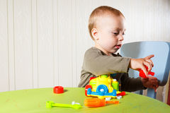 O rapaz pequeno repara o automóvel Fotos de Stock Royalty Free