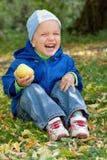 O rapaz pequeno ri e senta-se na grama. Foto de Stock