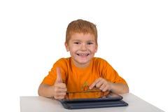 O rapaz pequeno senta-se com almofada e mostra-se o gesto Foto de Stock Royalty Free
