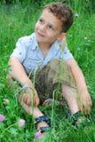 O rapaz pequeno senta-se em um gramado do trevo. Fotos de Stock
