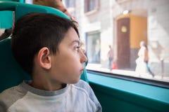 O rapaz pequeno senta-se na cadeira do ônibus que vai à escola Fotos de Stock Royalty Free