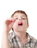 O rapaz pequeno suga o lollipop cor-de-rosa isolado Imagens de Stock