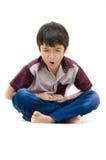 O rapaz pequeno tem a dor de estômago no fundo branco Foto de Stock