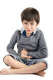 O rapaz pequeno tem a dor de estômago no fundo branco Fotografia de Stock Royalty Free