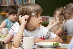 O rapaz pequeno tem um almoço Fotografia de Stock Royalty Free
