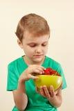 O rapaz pequeno toma a morango doce fresca da bacia Imagens de Stock Royalty Free