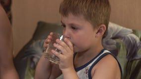 O rapaz pequeno toma a tabuleta e bebe a água O menino doente toma a tabuleta e bebe a água vídeos de arquivo