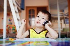 O rapaz pequeno toma um importante chama sua pilha fotografia de stock