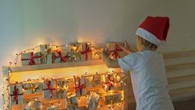 O rapaz pequeno toma um presente de um calendário do advento que pendura em uma cama que seja iluminada com luzes de Natal come?a vídeos de arquivo