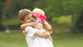 O rapaz pequeno tomam a menina em seus braços e assim que gire ao redor no parque Movimento lento video estoque