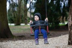 O rapaz pequeno triste, preocupado que balança só, saiu apenas desacompanhado, procurando pais fotos de stock