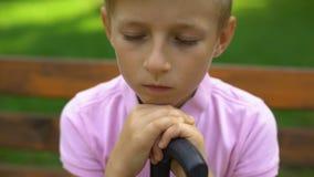 O rapaz pequeno triste que senta-se apenas, frustrado sobre tiranizar na escola, não tem nenhum amigo filme