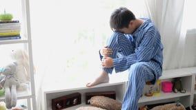 O rapaz pequeno triste tem um problema senta a parte dianteira sozinha da janela vídeos de arquivo