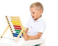O rapaz pequeno usa o ábaco para resolver problemas matemáticos fotos de stock
