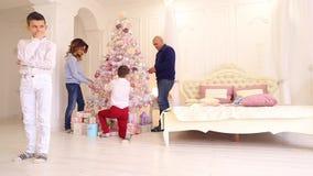 O rapaz pequeno vem acima com ideias para os presentes para o irmão e os pais, estando no quarto brilhante com a árvore de Natal  vídeos de arquivo