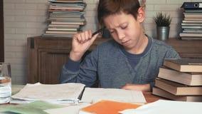 O rapaz pequeno vem acima com uma solução para o problema ao fazer trabalhos de casa filme