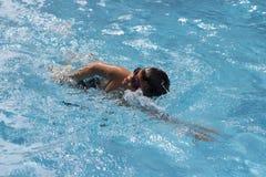O rastejamento dianteiro do menino asiático nada na piscina Foto de Stock