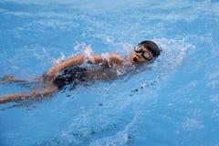 O rastejamento dianteiro do menino saudável nada na piscina Imagem de Stock