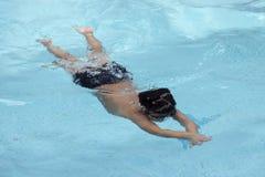 O rastejamento dianteiro do menino saudável nada na piscina Foto de Stock
