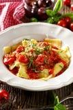 O ravioli enchido com vegetais grelhados cobriu com molho de tomate, queijo do padano do grana e a manjericão fresca Foto de Stock