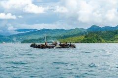 O rebocador pequeno leva o pontão para enviar aquele que ancora na baía de Padang fotos de stock